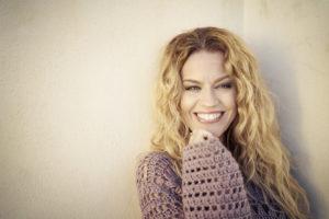 Hymyilevä sisustussuunnittelija Milla Alftan pitkissä vaaleissa hiuksissaan beigen seinän edustalla
