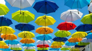 Lukuisia värikkäitä sateenvarjoja aurinkoisella taivaalla