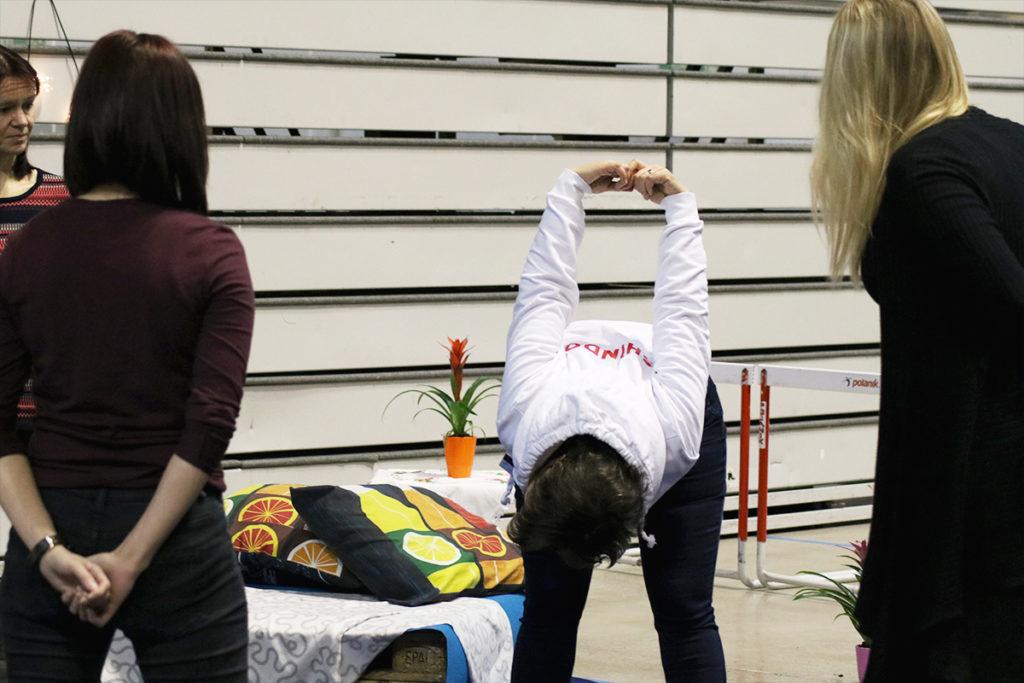 Shindo-rentoutuksen vetäjä venyttelee ja rentoutukseen osallistujat katsovat mallia.