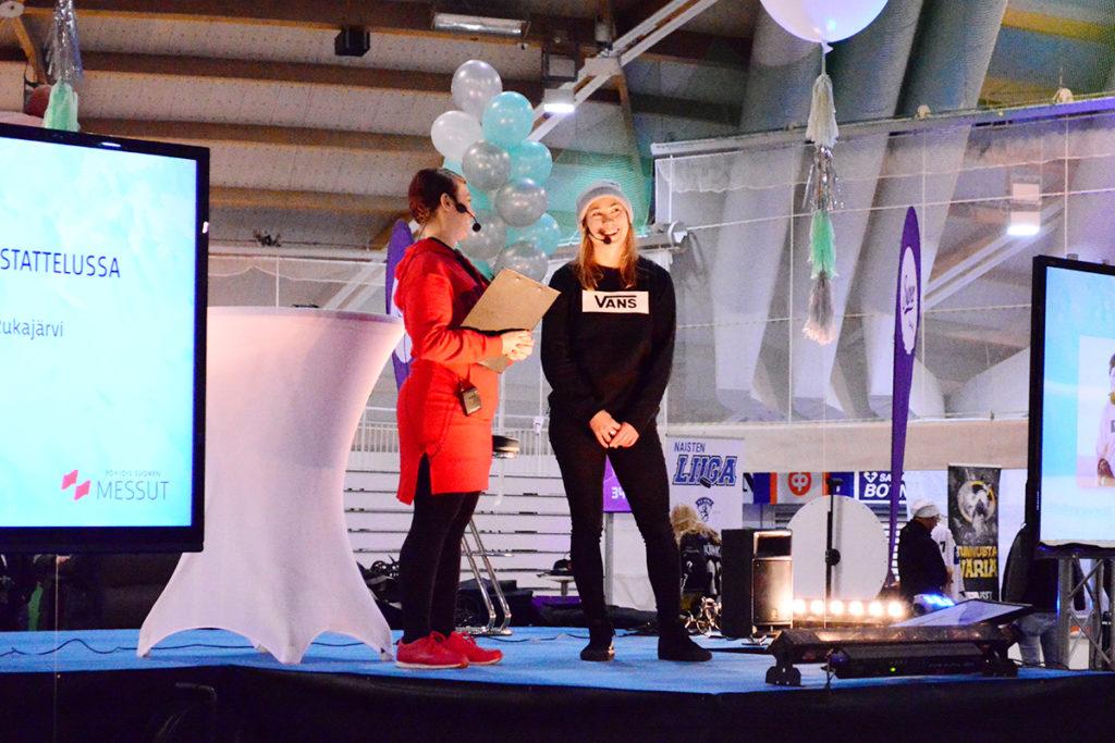 Enni Rukajärvi juontajan haastattelussa ohjelmalavalla