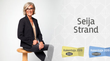 Sisustussuunnittelija Seija Strand hymyillen istumassa jakkaralla mustassa bleiserissä sekä Rakentaja 2019 Oulu ja Rakentaja 2019 Rovaniemi -logot valkoisella pohjalla
