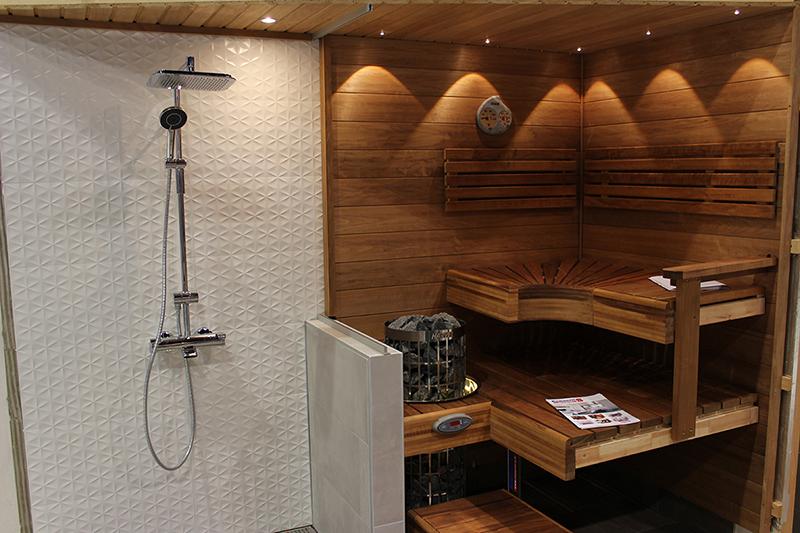 Tyylikäs pähkinäpuun sävyinen sauna sekä valkoisella seinällä sadesuihku