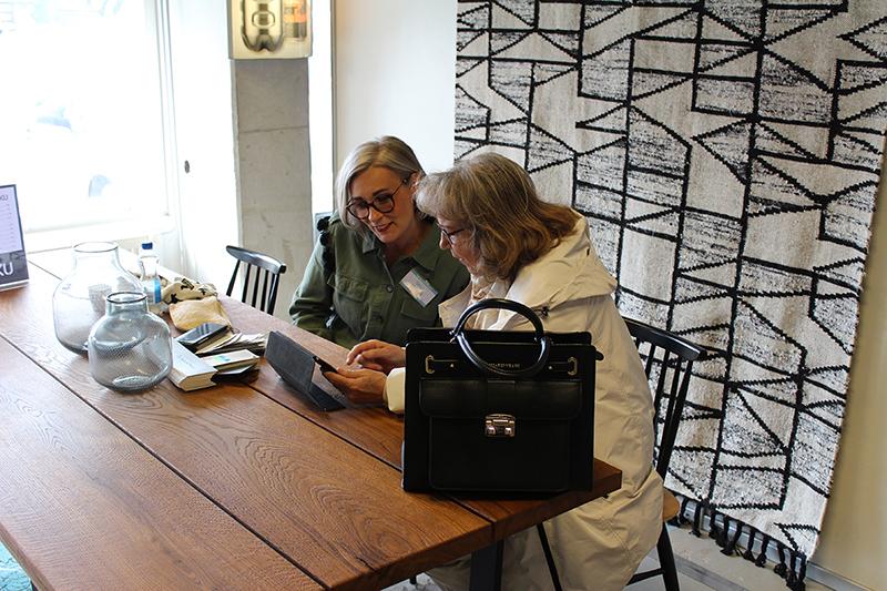 Sisustussuunnittelija Seija Strand keskustelemassa naisen kanssa pähkinäpuun värisen pöydän ääressä