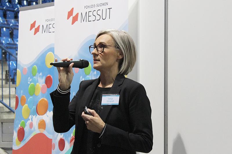 Sisustussuunnittelija Seija Strand keskittyneenä pitämässä puhetta yllään musta bleiseri