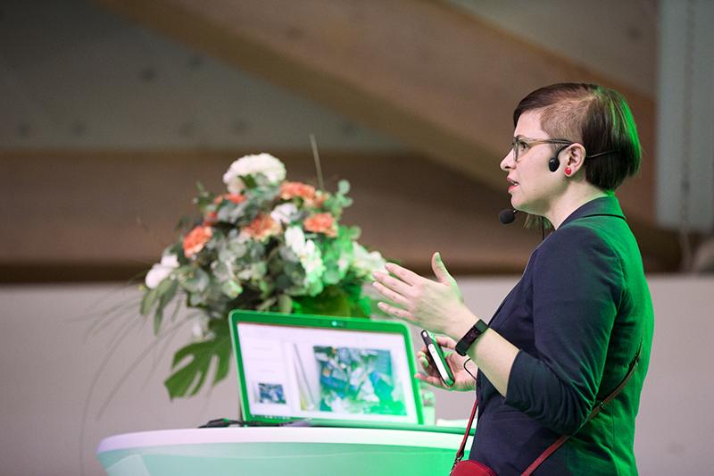 Ilana Aalto puhumassa keskittyneenä elehtien käsillään Rakentaja 2019 Oulu -tapahtumassa
