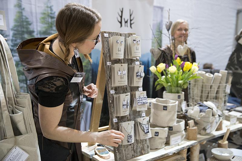 Nainen messuosaston pöydän edessä ruskea designpuku päällään esittelemässä lappi aiheisia tuotteitaan