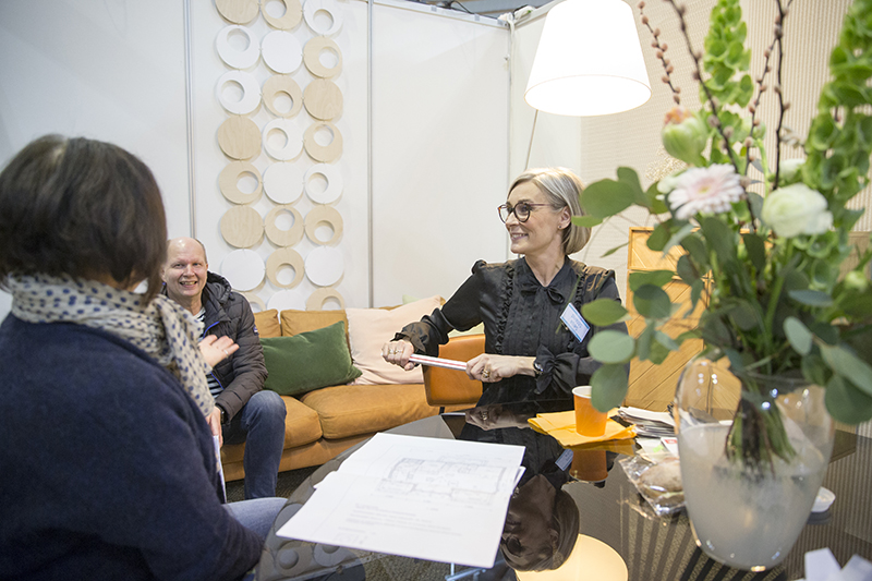Sisustussuunnittelija Seija Strand keskustelemassa messuosastollaan kahden messuvieraan kanssa