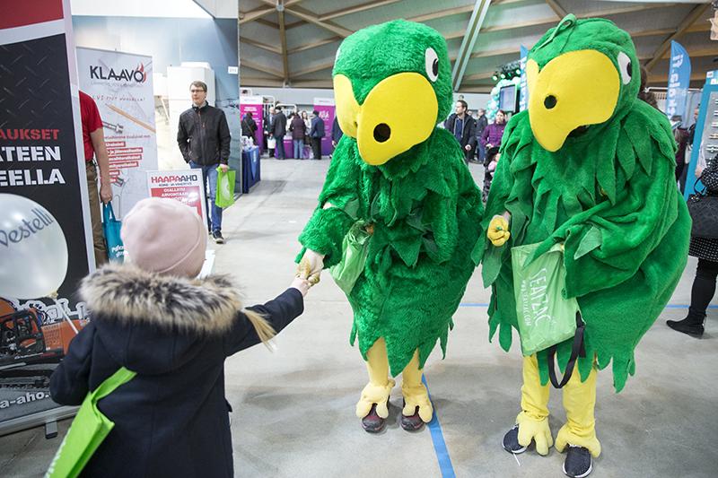 Kaksi papukaijaksi pukeutunutta ojentamassa pipopäiselle lapselle karkkia messukäytävällä