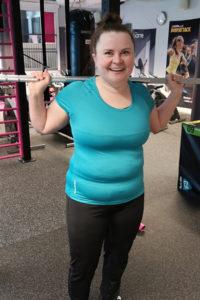 Nainen turkoosissa paidassa seisomassa hartioillaan kuntosalitanko