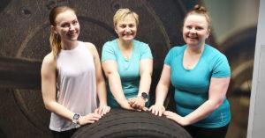 Kolme hymyilevää naista urheiluvaatteissa