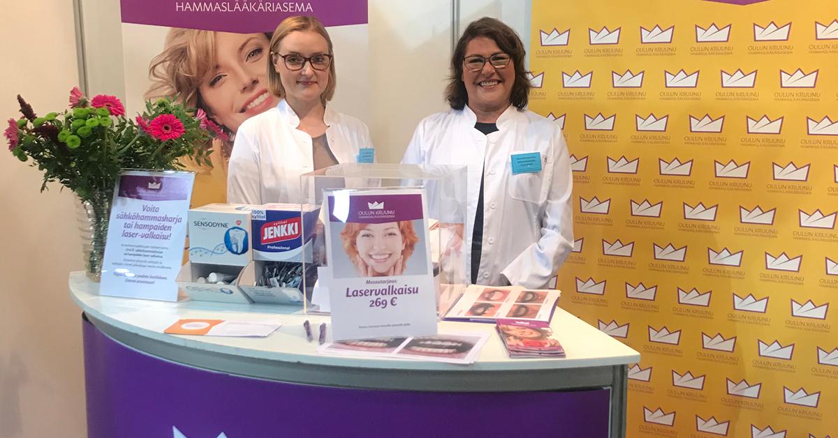 Kaksi hymyilevää naista keltaisen messuosaston edessä sonnustautuneena valkoiseen lääkärin -takkiin