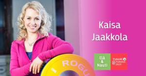 Kaisa Jaakkola pinkki huppari päällään leveästi hymyillen nojaa levypainoon vieressään Elä & Nauti | Tykkää & Tuhulaa logo