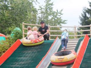 Isän katsoessa kolme lasta laskemassa mäkeä Vauhtipuiston mäenlasku tyynyillä