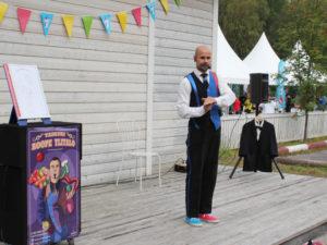 Värikkääseen pukuun sonnustautunut Taikuri suorittamassa taikatemppua esiintymislavalla Vekkulit Vestarit -tapahtumassa