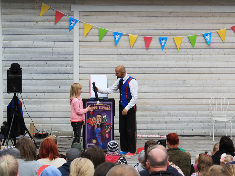 Värikkääseen pukuun sonnustautunut Taikuri suorittamassa taikatemppuaan lavalla avustajansa kanssa