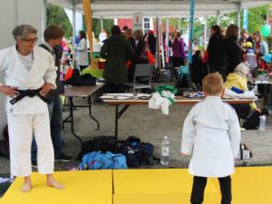 Judo pukuun sonnustautunut nainen ja pieni poika harjoittelevat judon alkeita judomatolla Vekkulit Vestarit -tapahtuman teltassa